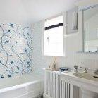 Біле панно з синім малюнком розбавляє стерильно білий колір ванній