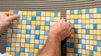 Процес приклеювання плитки мозаїки на стіну у ванній
